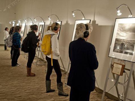 people observing photographs in art gallery with headphones on