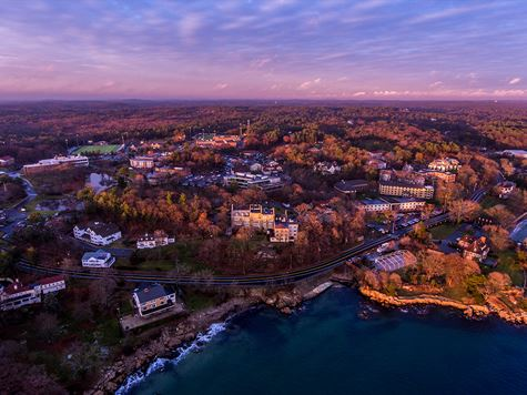 aerial shot of campus from over ocean during sunset