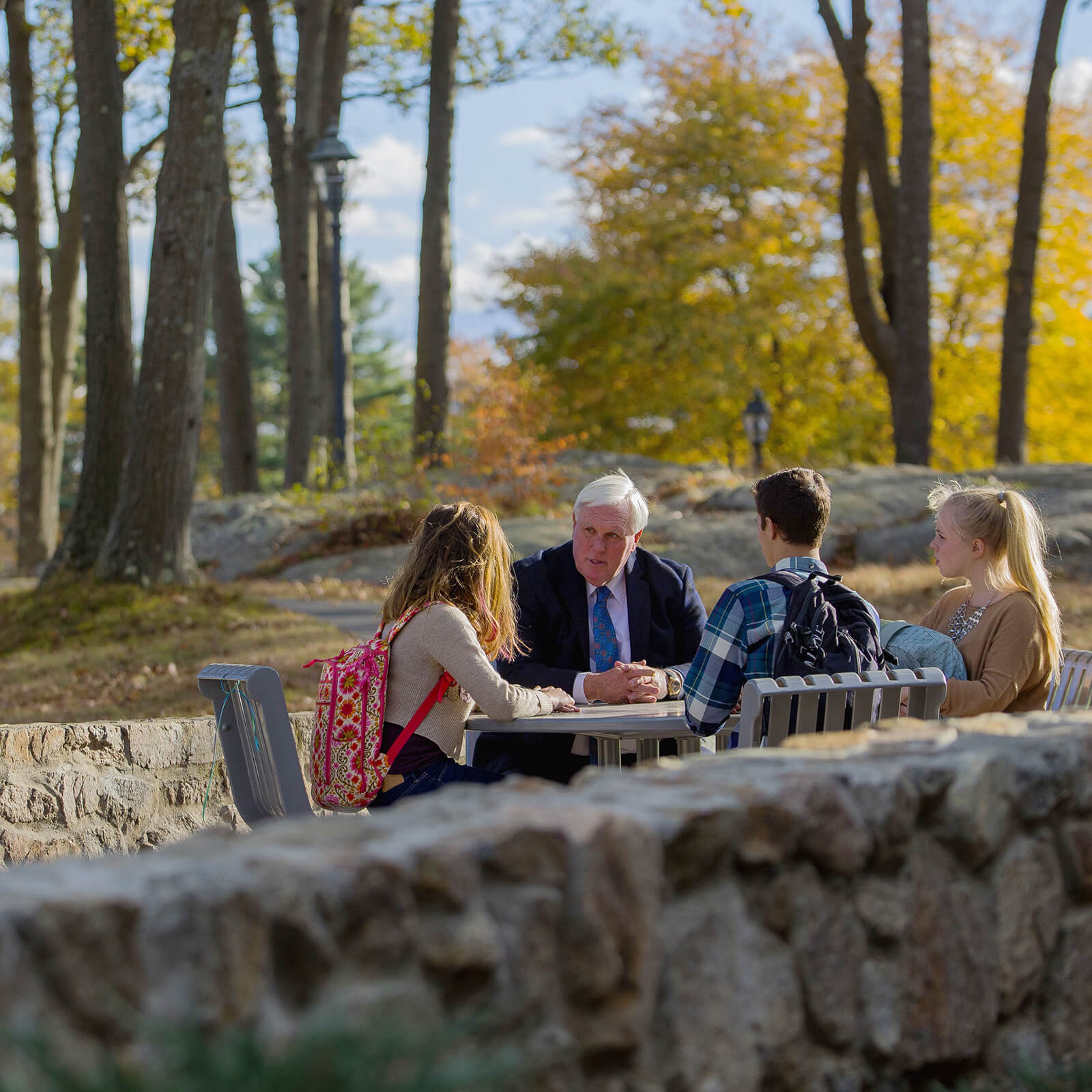 Dr. Wylie and 3 students sitting at a table outside and talking