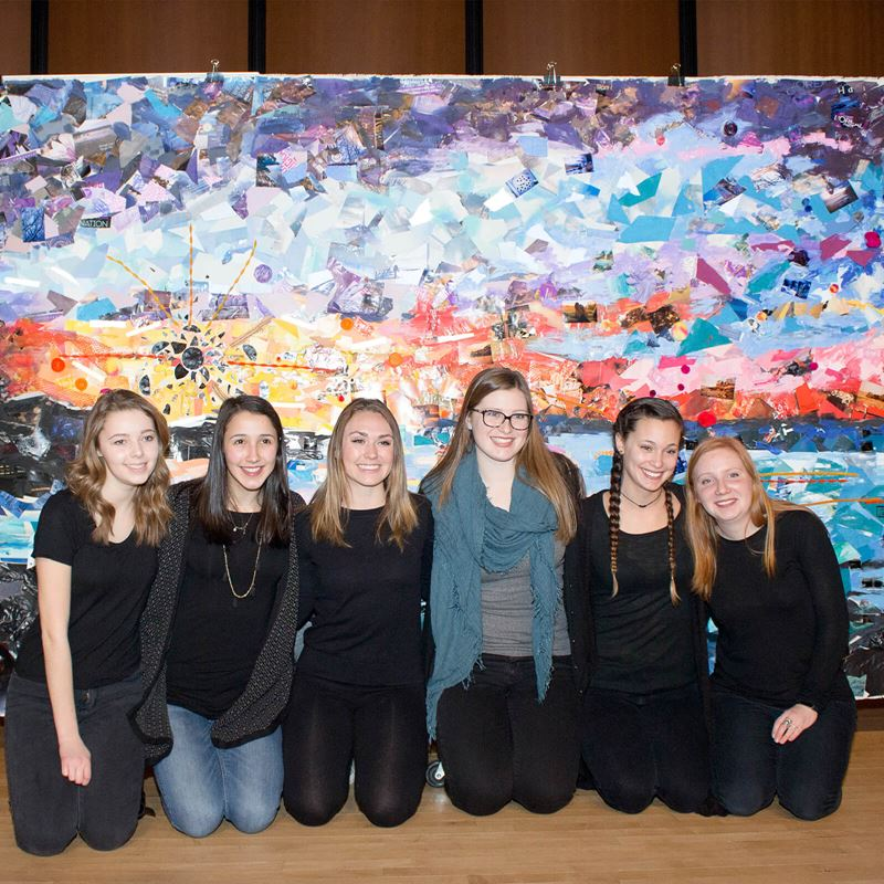 6 students kneeling in front of large art piece