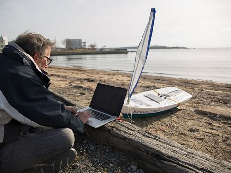 professor working on solar powered boat on laptop on endicott beach