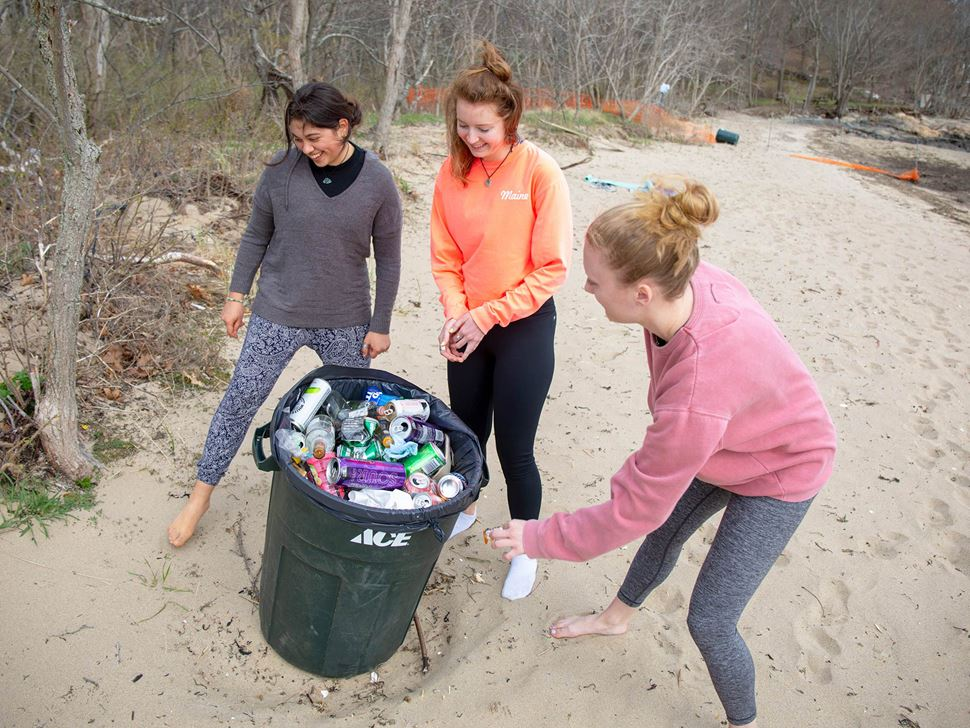 hree Endicott  students cleaning up waste at the beach near Tupper Hall