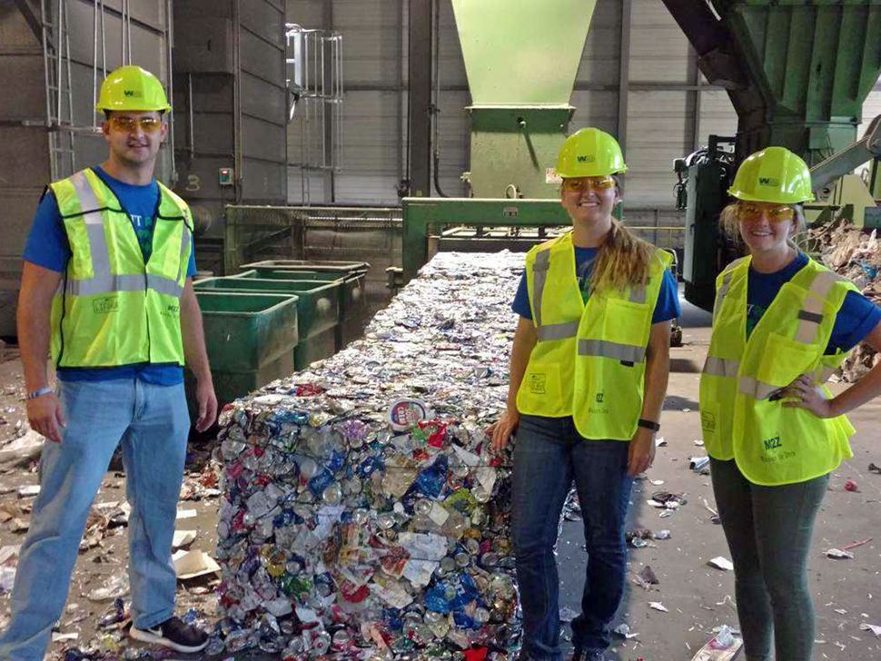 Three individuals in reflective gear at the WM Recycling facility