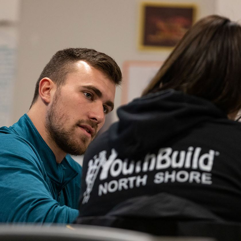 "male intern teaching a student wearing a black ""youth build north shore"" tee shirt"