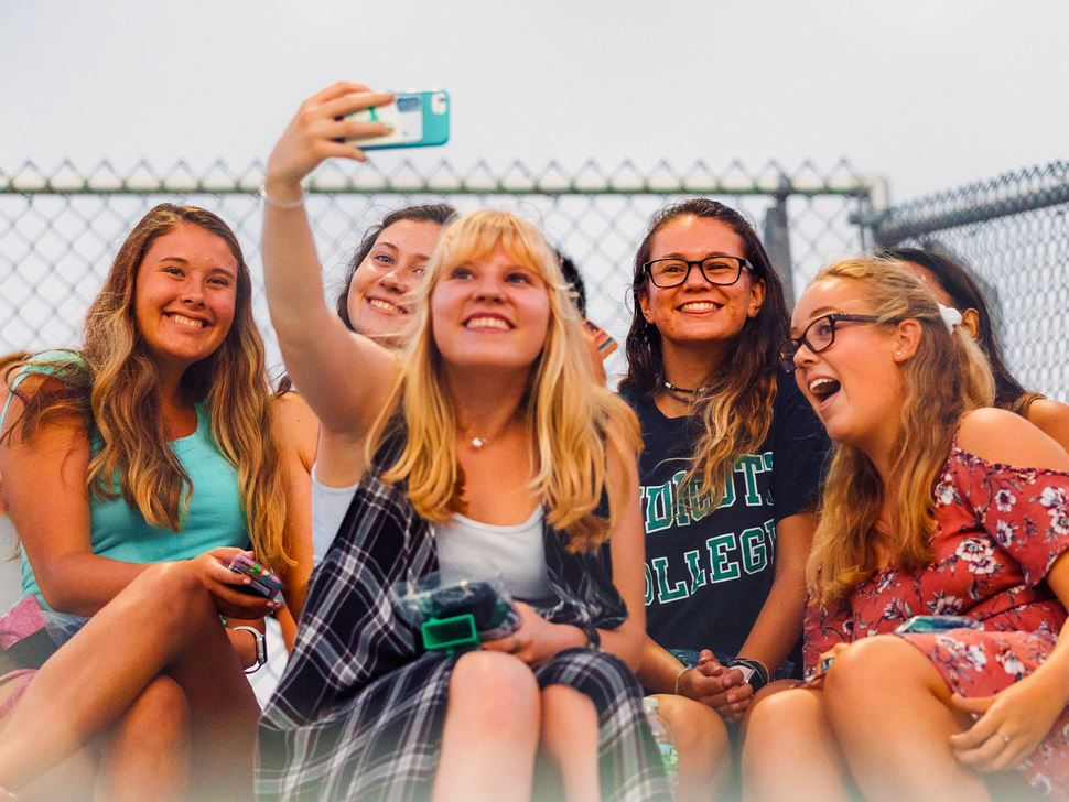 Six students posing for a selfie at an athletic event