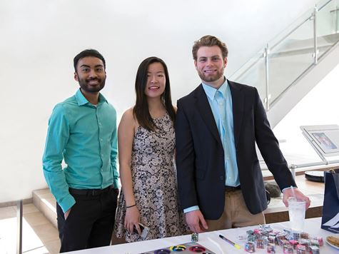 three students dressed up manning a table at event