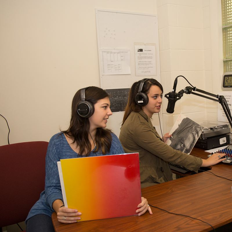 two students working in radio station with headphones on one holding a record case