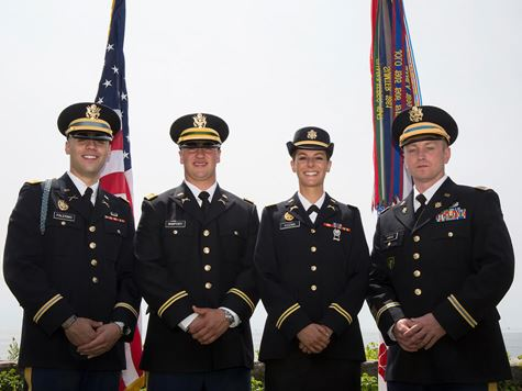 four members of the armed forces in uniform in front of the flags