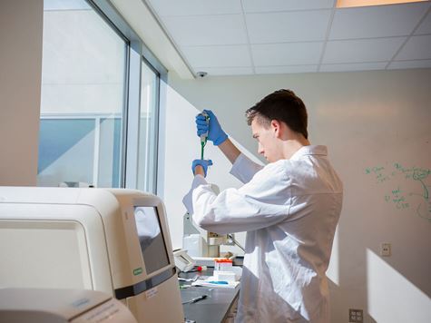 student researching in laboratory with machines and white coat on