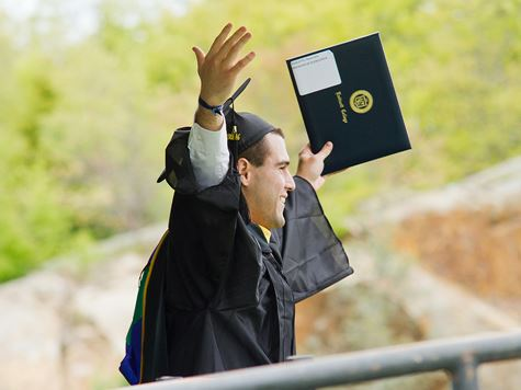 student holding up his diploma at graduation