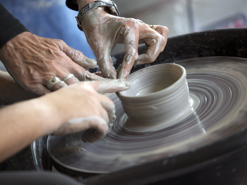 close up shot of two people working on a clay piece on potter's wheel