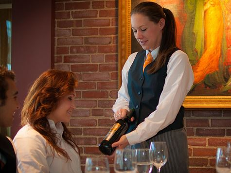 hospitality student offering wine to customer at la chanterelle restaurant at misselwood