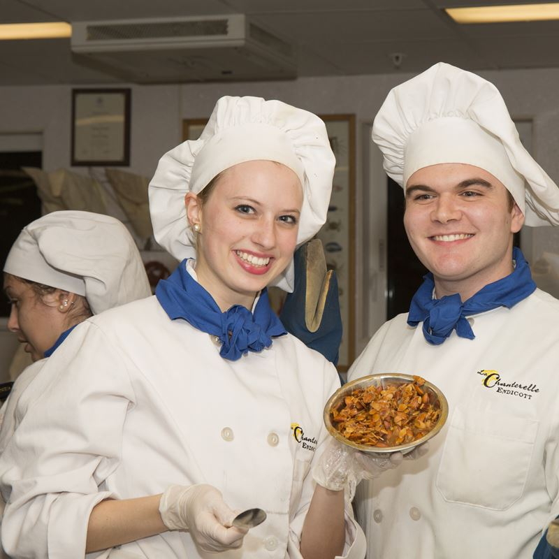 two culinary students dressed in cooking attire holding up sample dish