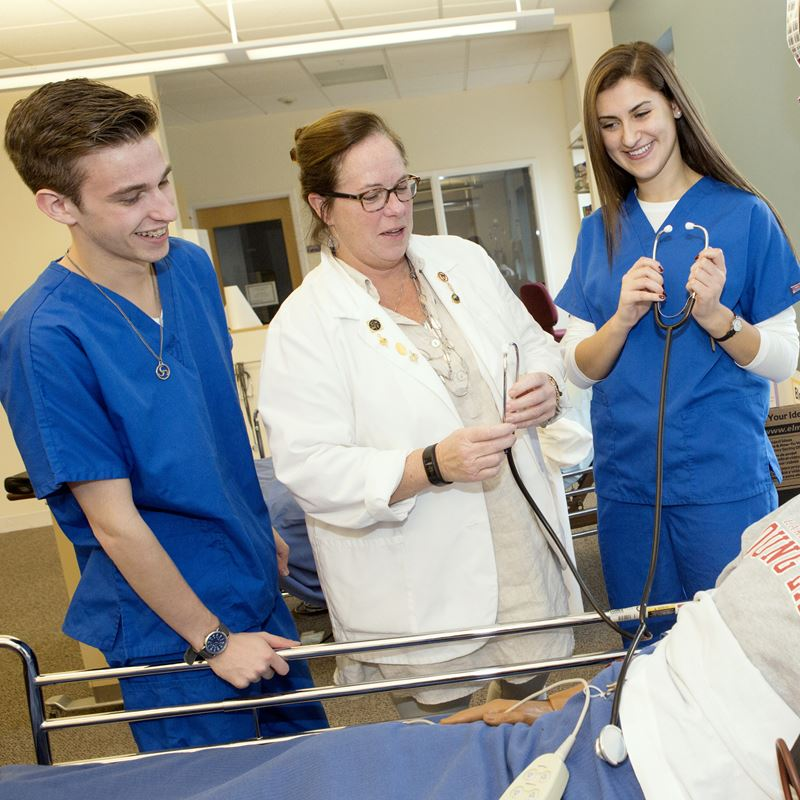 two nursing students in scrubs observing teacher working with dummy