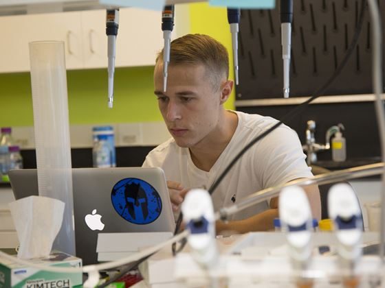 student studying on laptop in laboratory