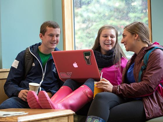 three students socializing and working on laptop in lounge area