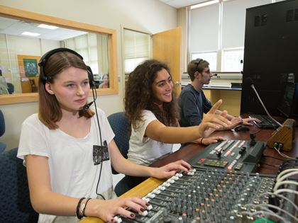 students working in sound booth with headphones
