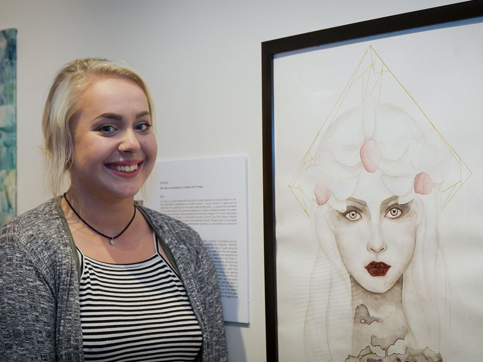 an arts therapy student in front of her portrait