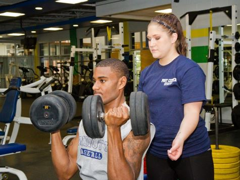 a girl watching and helping a guy lift weights