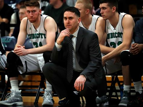 the gulls basketball coach squatting in front of his bench