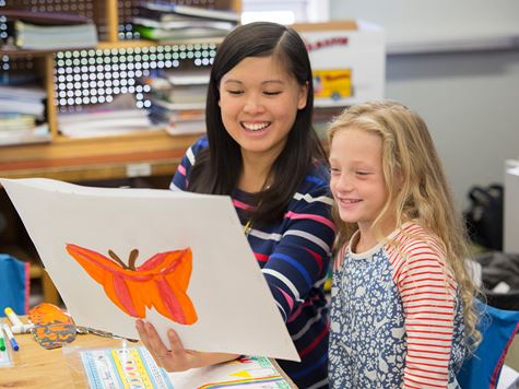 an early childhood education student looking at a kid's butterfly drawing
