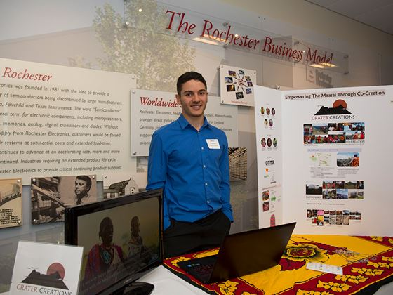 a guy presenting a booth about the rochester business model