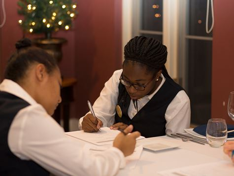 two hospitality management students writing in a book
