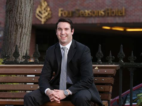 a man in a business suit sitting on a bench in front of the four seasons hotel
