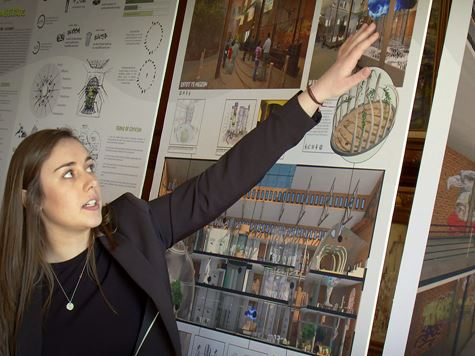 a woman pointing and explaining the interior design works on the wall