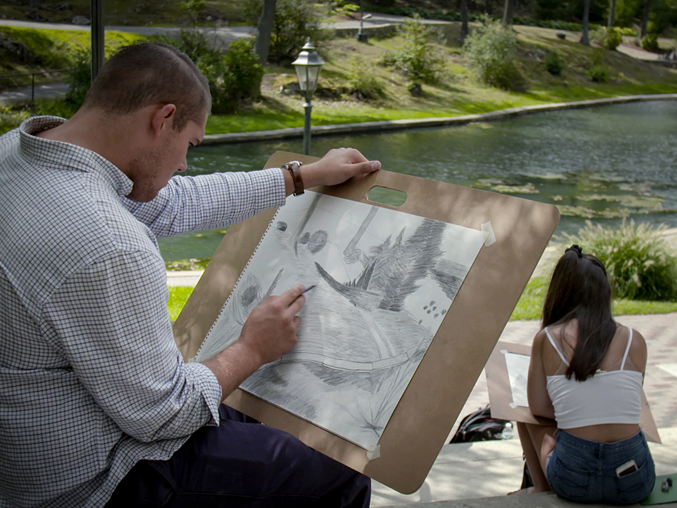 a guy sitting down outside with a board and drawing on paper