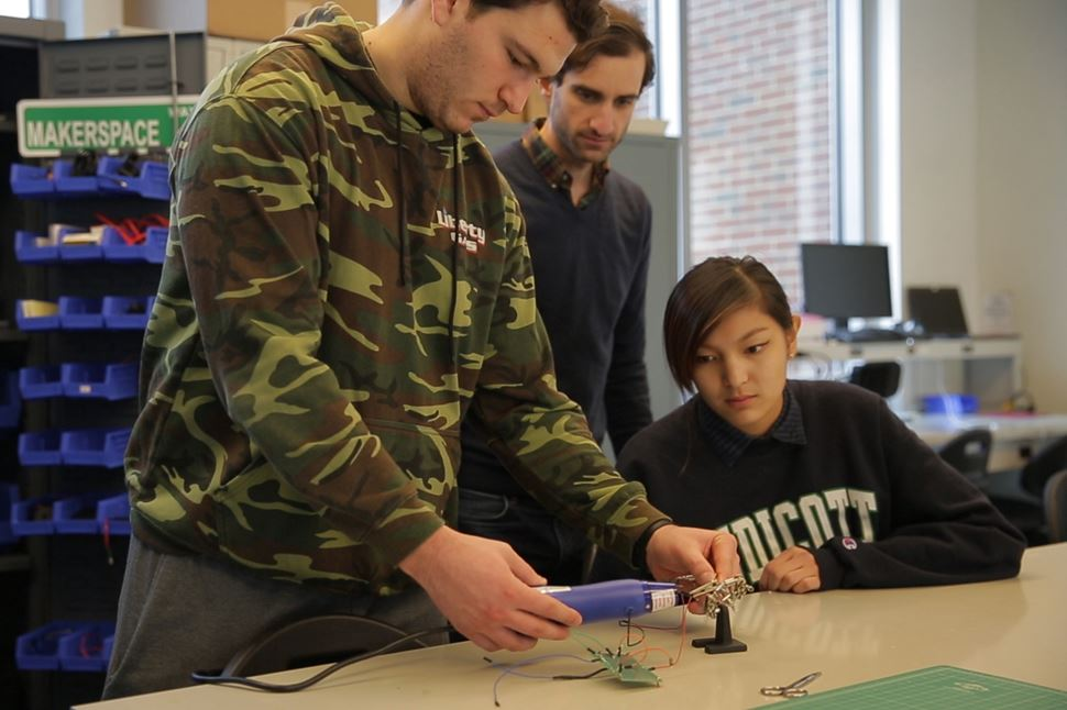 Makerspace at Endicott College with three students working on creating a project with state-of-the-art equipment.