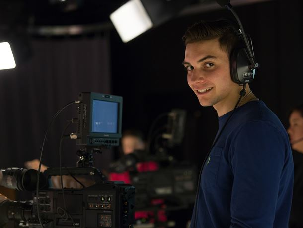 An Endicott College student smiles while filming