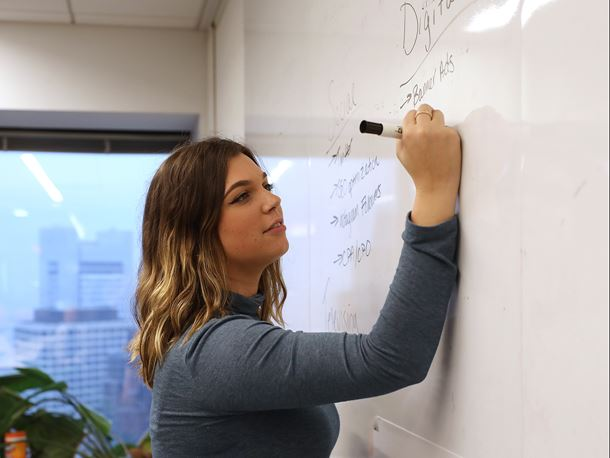 An Endicott College student writes on the whiteboard