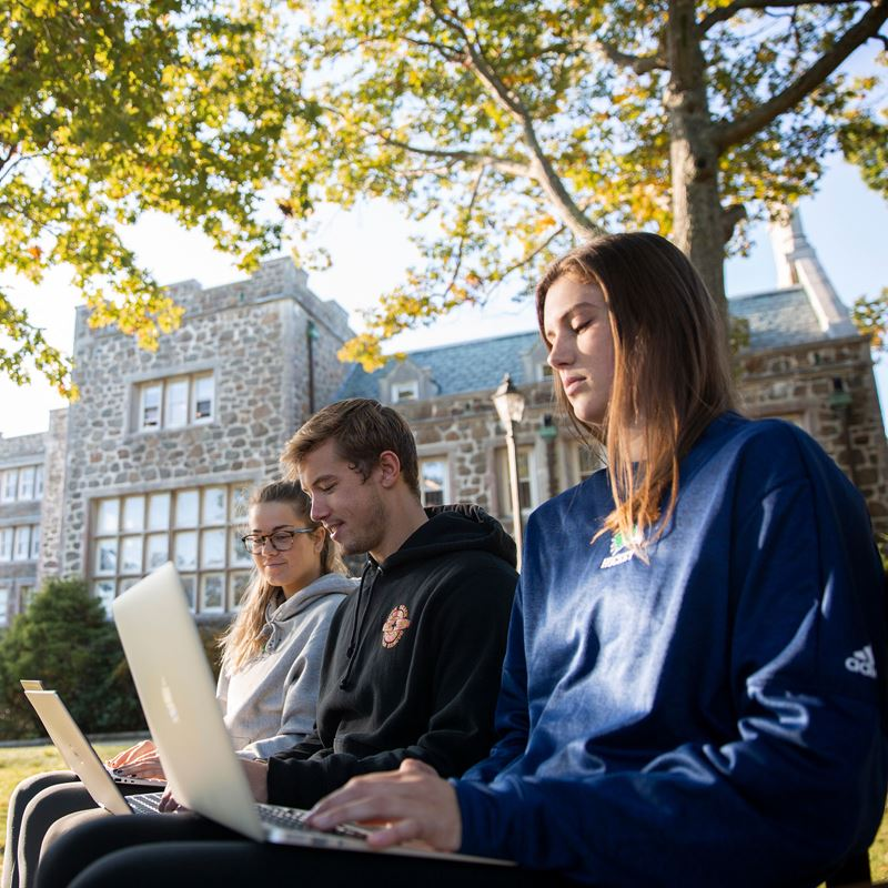 Three students looking at their laptops outside College Hall