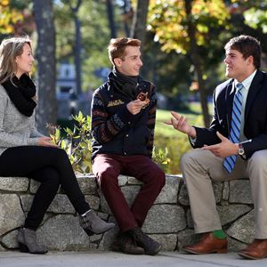 fall shot of student sitting and talking with two professors