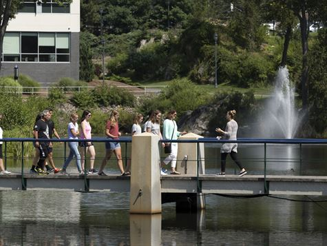 student walking across bridge over pond during  campus tour
