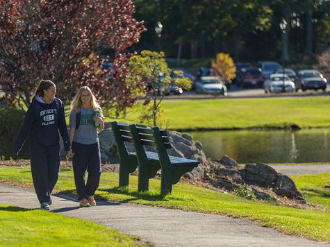 two students talking and walking down path next to pond on campus