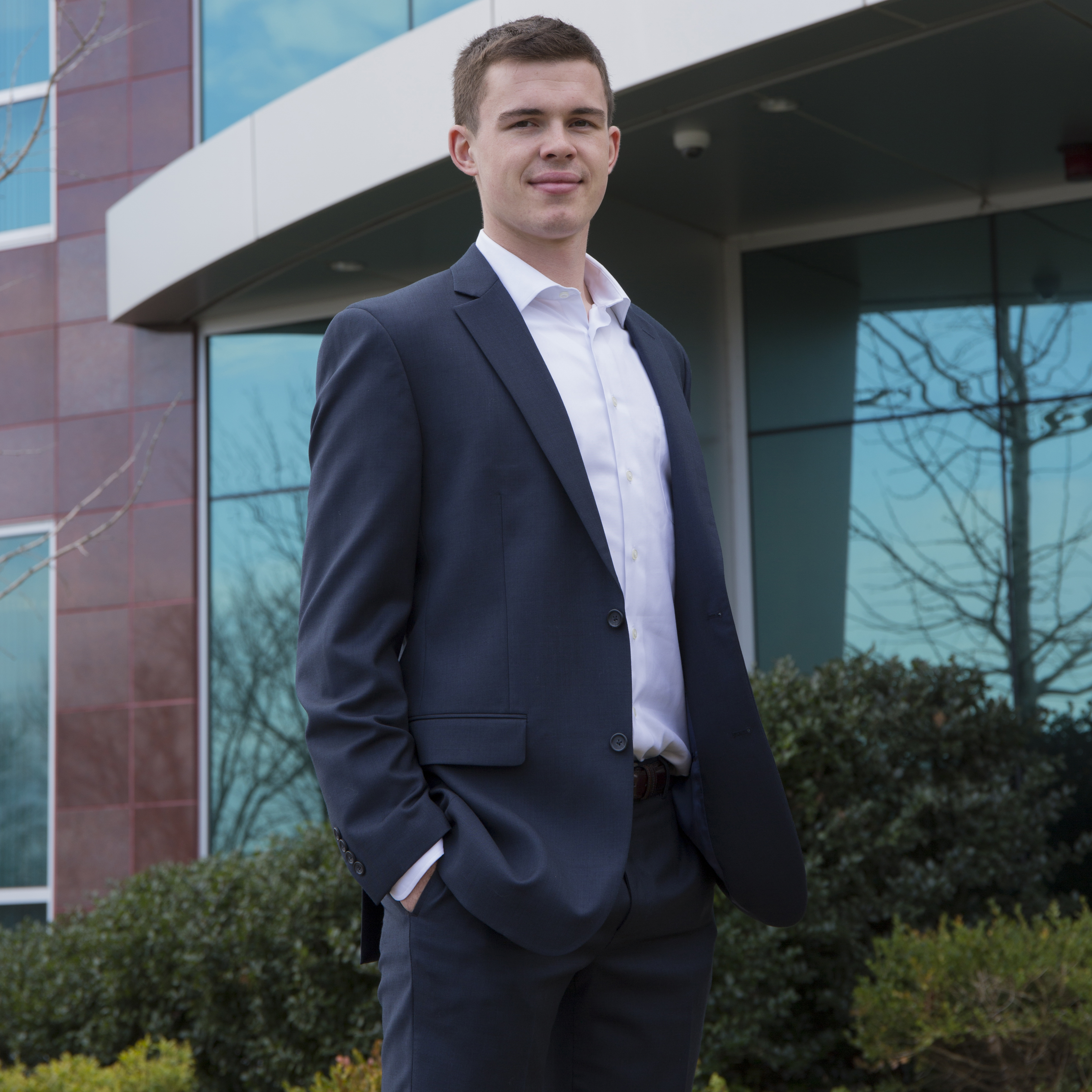 student in suit standing outside of internship building