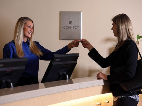 a woman handing a card key to a customer for her hotel room
