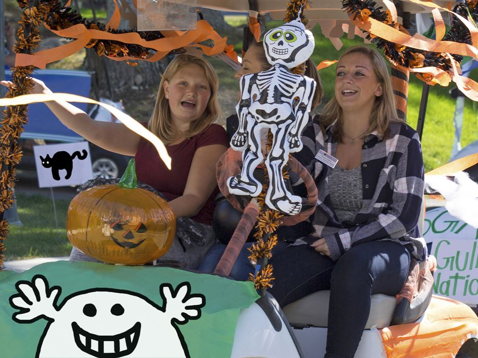 two women riding in a Halloween-themed golf cart