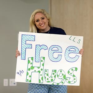 a woman holding a 'free hugs' sign
