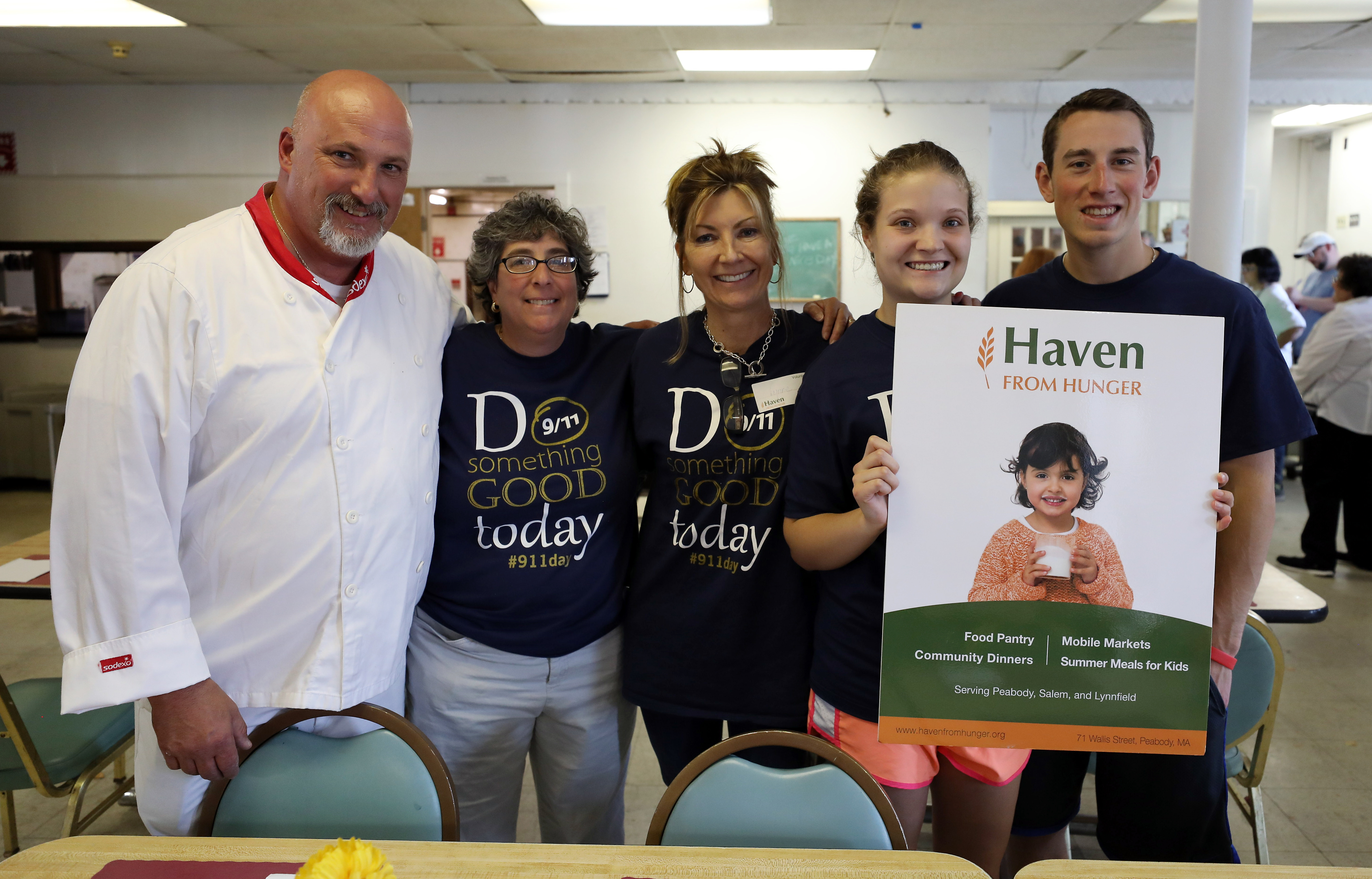 a chef and four others posing for a photo with a 'Haven from Hunger' sign