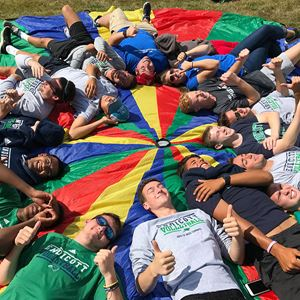 a group of people laying on a multicolored circular sheet