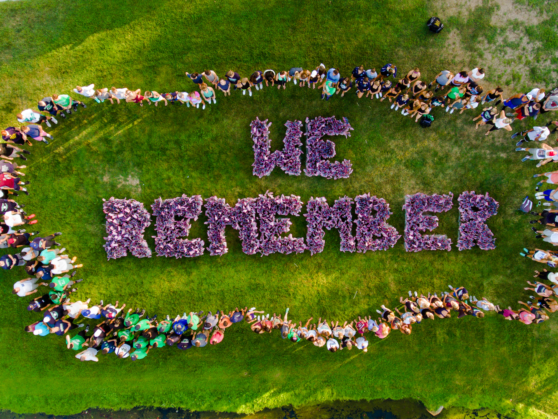 a top-down view of many people standing around the words 'we remember' spelled out with US flags