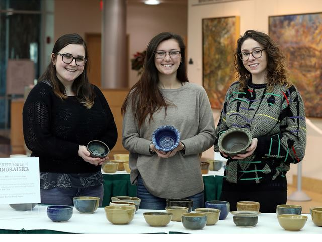 Students hold handmade ceramic bowls at the Empty Bowls Fundraiser in the Walter J. Manninen Center for the Arts atrium