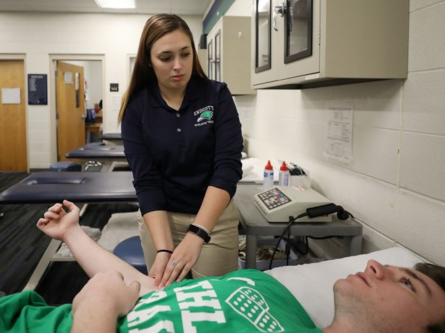 Jennifer Holman '18 works with an athlete in Endicott's athletic training room.