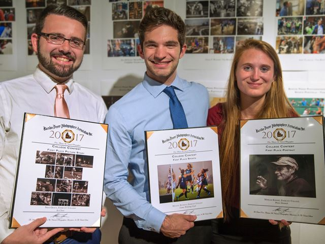 three student winners of the Boston Press photography contest display their plaques