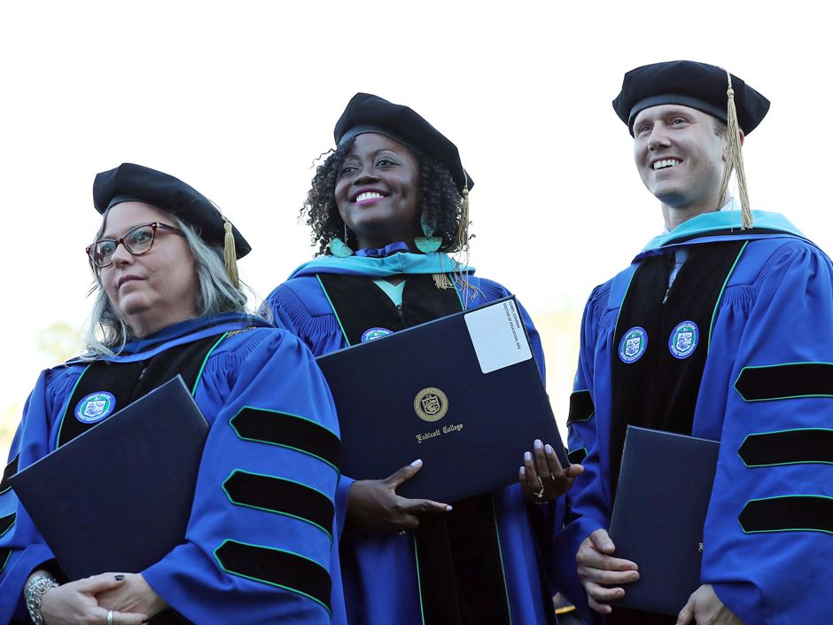 three doctoral graduates pose at commencement with their diplomas