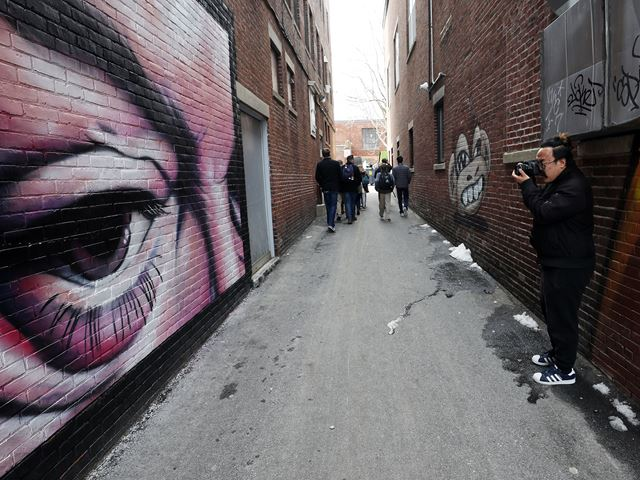 Students in The Point in Salem walking through an alley with murals.