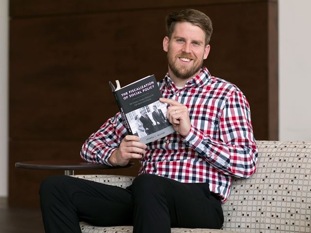 Joshua McCabe holding his first book.